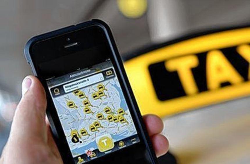 Ein Smartphone mit der geöffneten App MyTaxi vor einem Taxi-Schild.