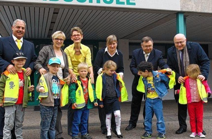 Sicherheitswestenübergabe an Erstklässler: Unser Bild zeigt (von links) Rainer Sattelberger (Post), ...