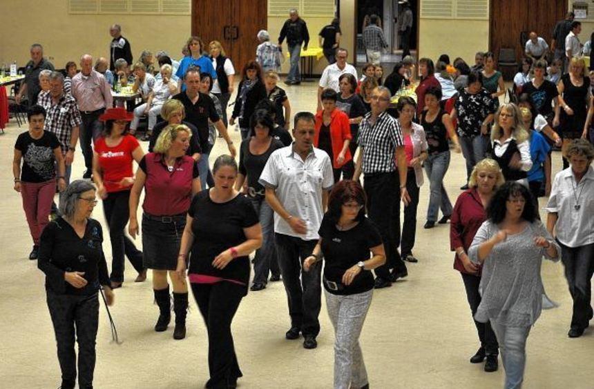 In einer Reihe aufgestellt bewegen sich die Anhänger des Linedance zu den bekannten Schritten. ...