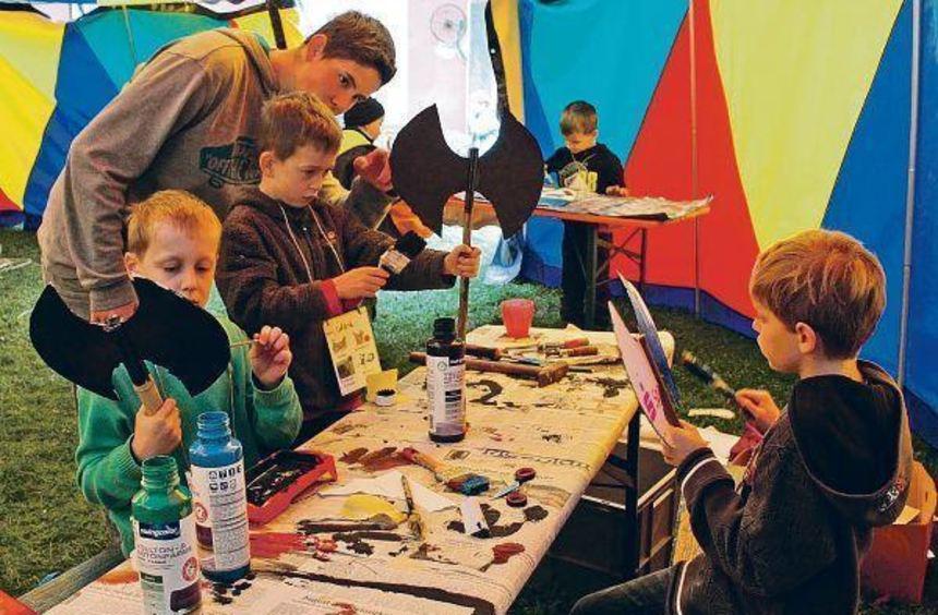 Bei der Ferienaktion des Museums basteln Kinder eine Doppelaxt (l.), bauen Raketen (r.,v.o.), Autos ...