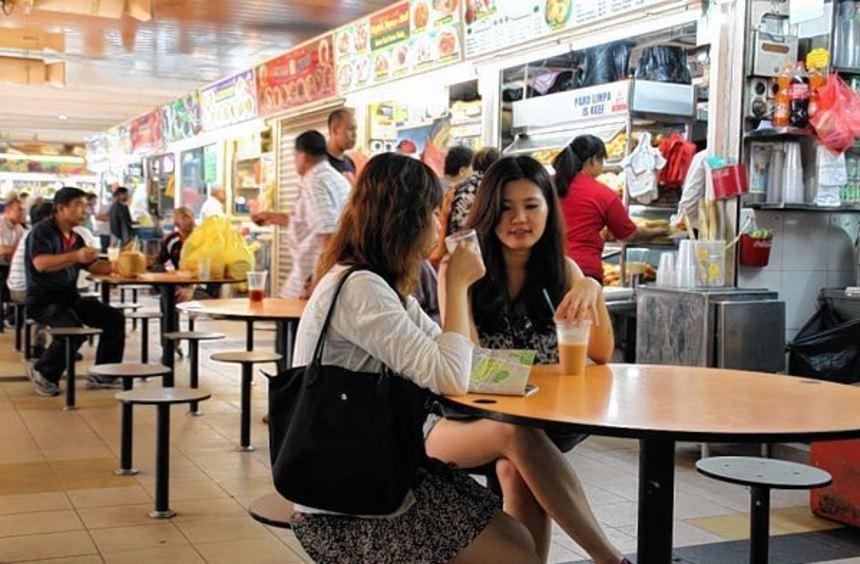 Gäste sitzen an Tischen vor Garküchen in Singapur. Garküchen sind ein Wahrzeichen Asiens.