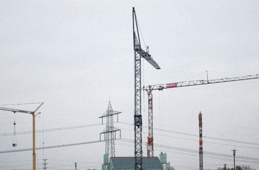 Baukräne weisen den Weg ins neue Baugebiet, das nun mit dem obligatorischen Schnitt durchs Band von ...